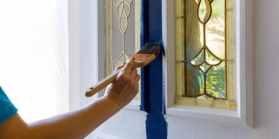 man painting front door blue