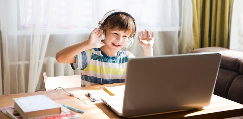School boy wearing headphones on video call