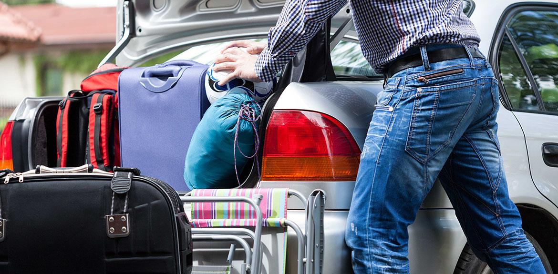 man loading car bags luggage