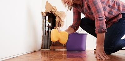 Woman cleaning up after water leak