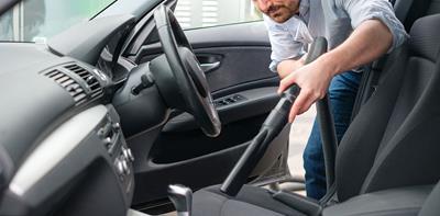 man vacuuming car seats