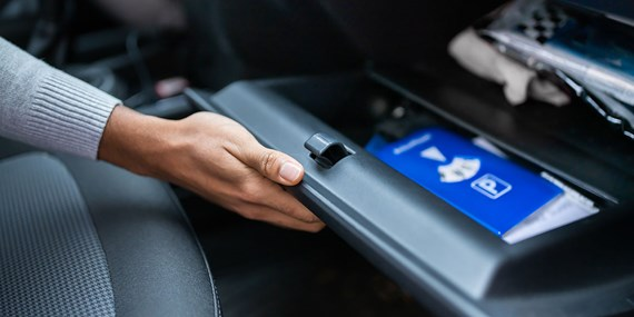 woman's hand opening car glove box