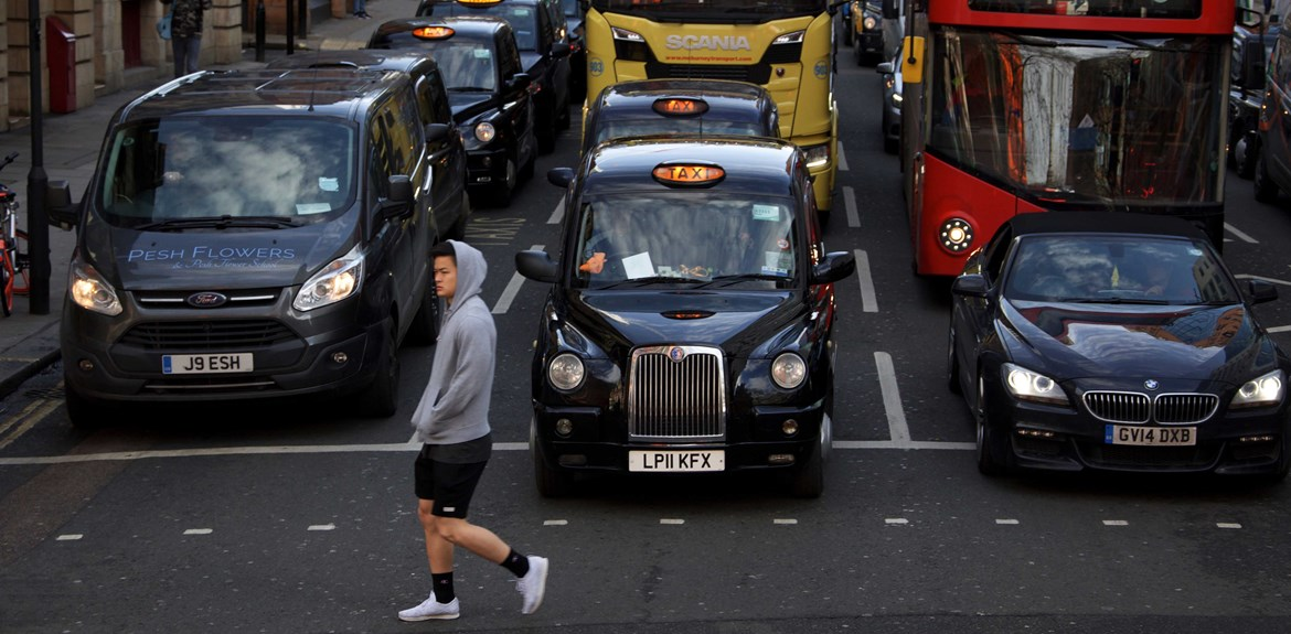 Man walking past London traffic taxis cars and buses