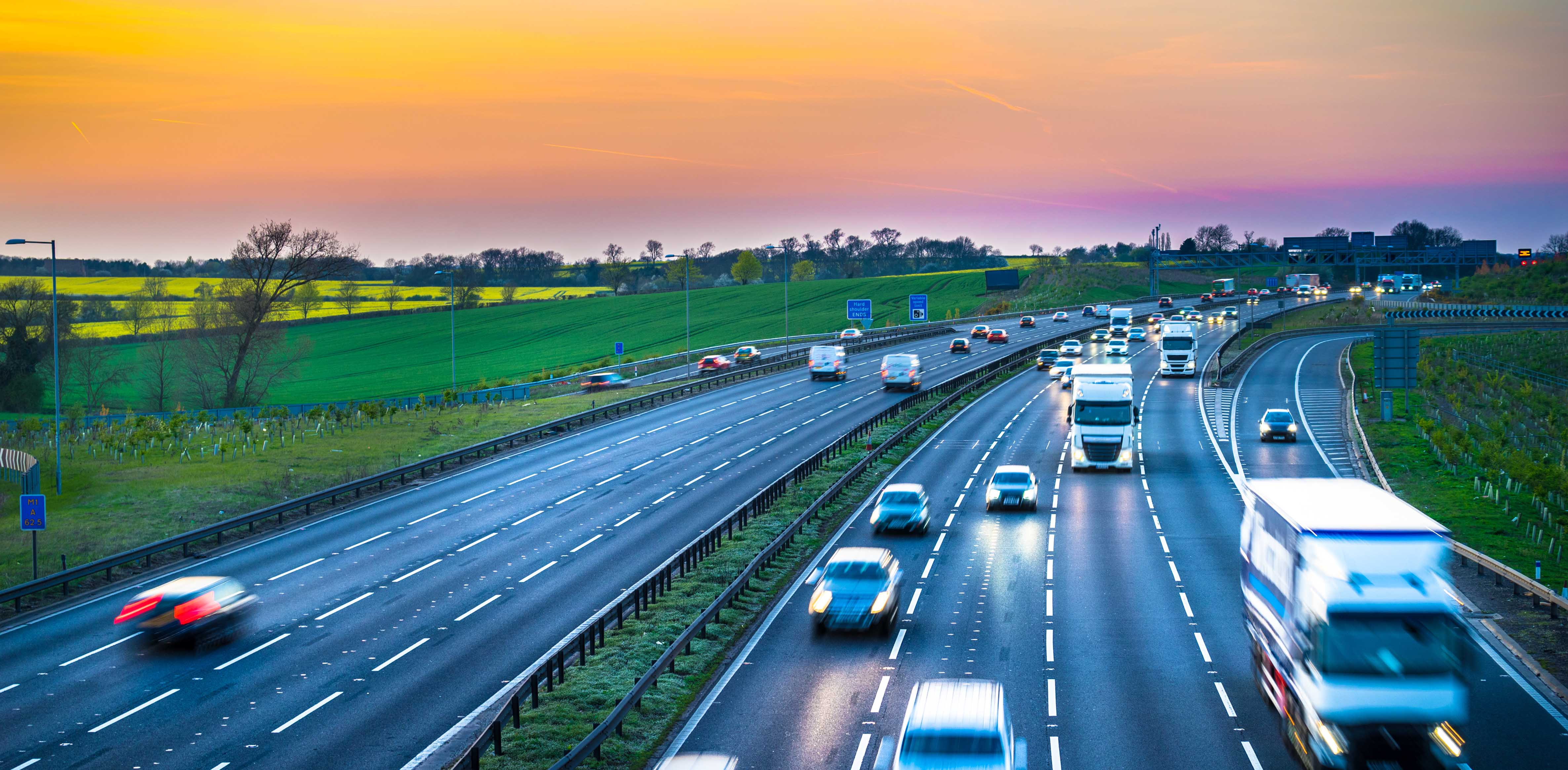 busy motorway lorries cars sunset