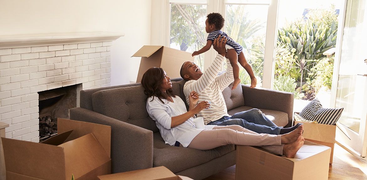 family moving home boxes holding child