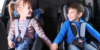 two children smiling on family road trip