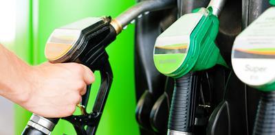 Driver picking up pump nozzle at a petrol station