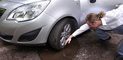 man inspecting car damage after hitting a pothole