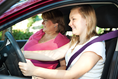 young woman learning to drive with mother next to her