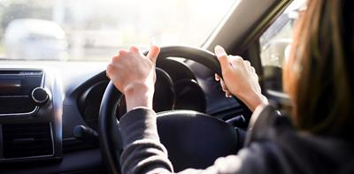 woman driving car with hands on steering wheel