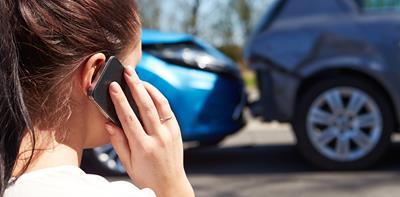man inspecting car damage following a car accident