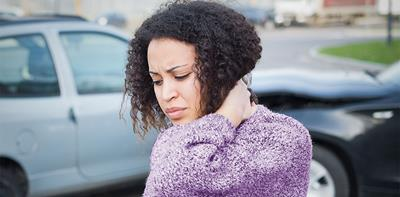 woman holding neck in pain following car accident