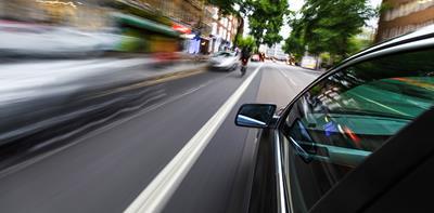 Black car speeding past blurry cars