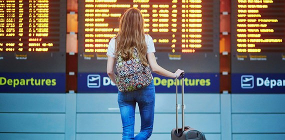 woman looking at airport departure boards